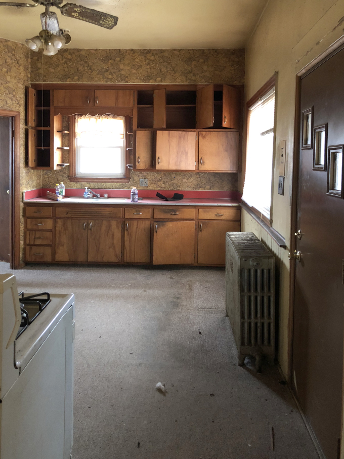 This worn down kitchen with outdated wallpaper and paint colors needs a major update.