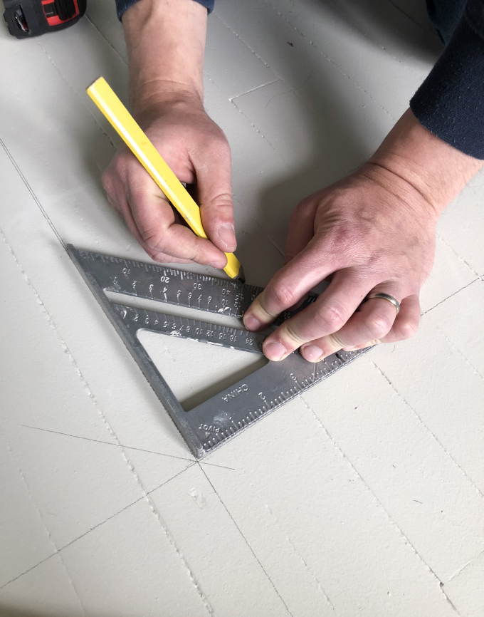 measuring out the pattern for the painted wood floors
