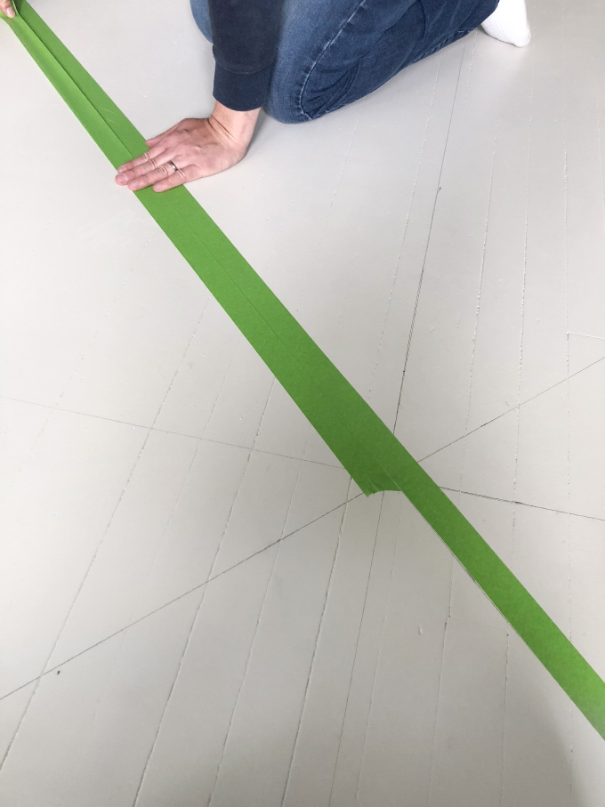 taping down the pattern for the painted wood floors