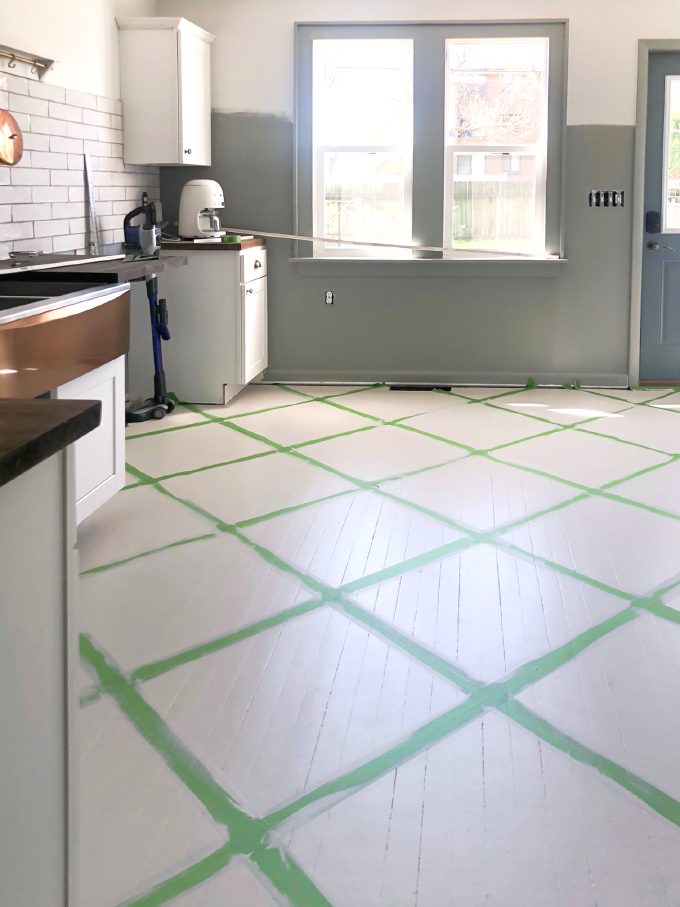 the full room with tape on the ground for the pattern on our painted wood floors