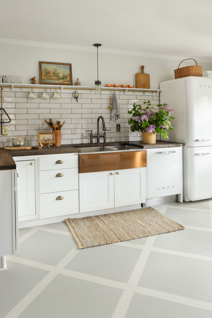painted wood floors with rug in front of farmhouse sink