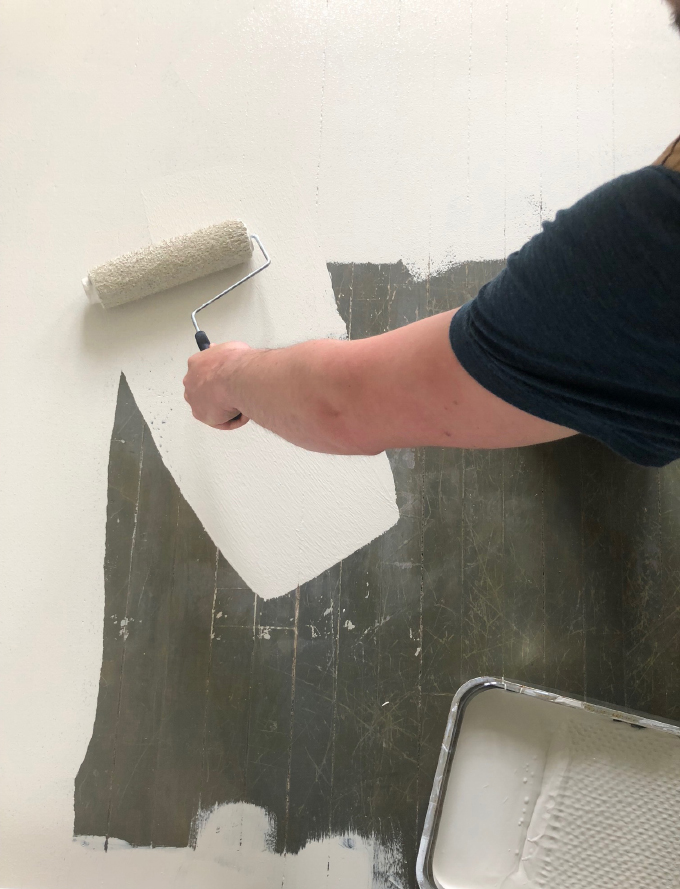 using a roller to put the paint on the floor