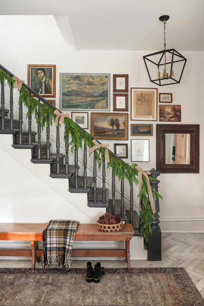 a farmhouse staircase with a gallery wall decorated for Christmas from I Spy DIY